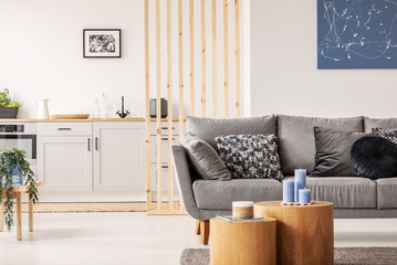 Open plan studio apartment with small white kitchen and living room with grey couch and wooden coffee table