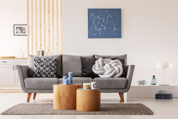 Blue abstract painting on white wall of contemporary living room interior with grey settee with pillows