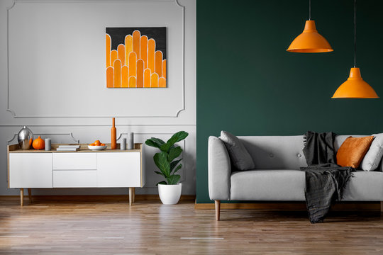 Abstract orange painting on grey wall of stylish living room interior with white wooden furniture and grey couch