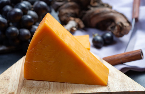 Piece of hard orange Cheddar cheese close up