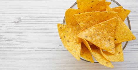 Full bowl of tortilla chips on white wooden background, top view. Mexican food. Copy space.