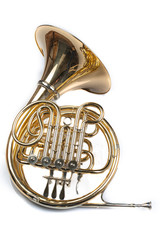 French horn on a white table. Beautiful polished musical instrument.