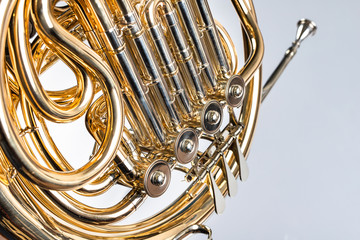 French horn on a white table. Beautiful polished musical instrument. Wall mural