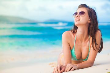 portrait of long haired woman in bikini and sunglasses lying on tropical beach. La Digue, Seychelles
