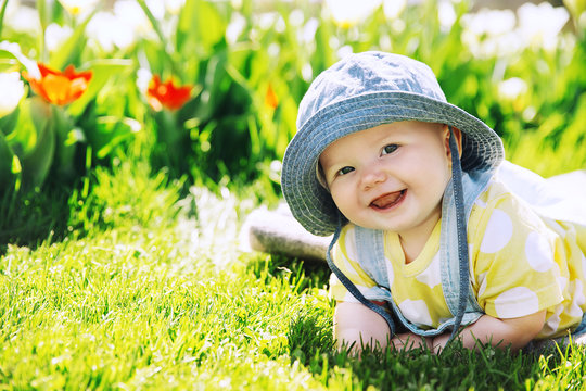 Baby in green grass of tulip field at springtime