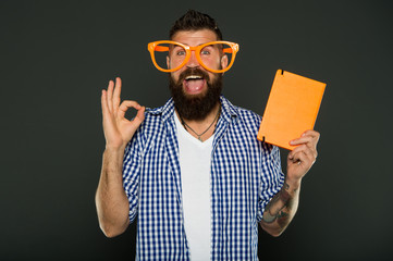 Book cover copy space. Hipster bearded man wear funny eyeglasses hold notepad or book. Bright up your day. Read this book. Comic and humor sense. This story just made my day. Funny book for relax