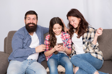 Parental advisory. Family spend weekend together. Child little girl use smartphone with parents. Friendly family having fun together. Mom dad and busy daughter relaxing on couch. Family leisure