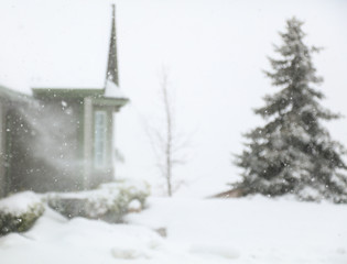 A blizzard in the mountains with snow blowing off of the roof.