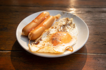 Easy breakfast set of fried egg and sausages in a dish.