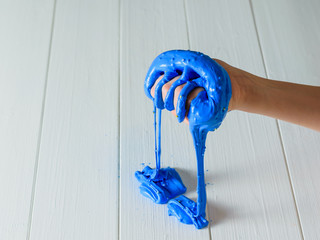 The blue slime flows from the child's right hand onto the white table.