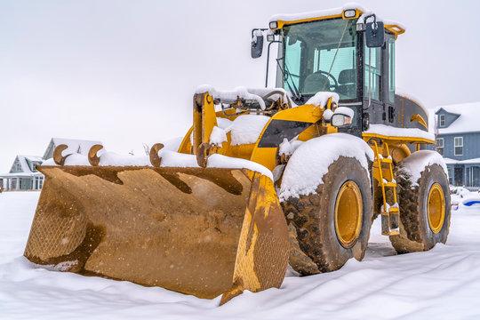 Loader against snow and homes in Daybreak Utah