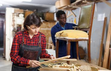 Artisans in process of renewing armchair