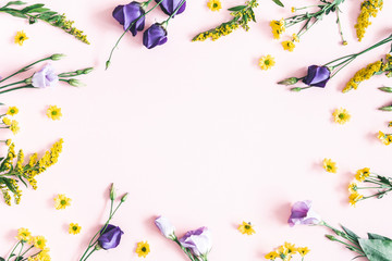 Flowers composition. Yellow and purple flowers on pastel pink background. Spring, easter concept. Flat lay, top view, copy space