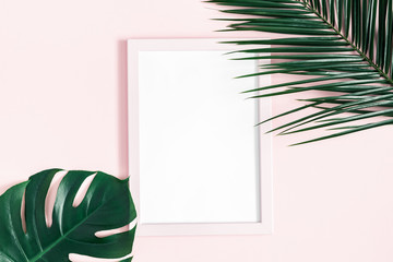 Summer composition. Tropical palm leaves, photo frame on pink background. Summer, nature concept. Flat lay, top view, copy space