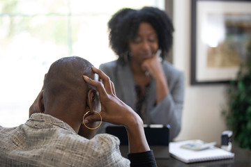 Black female client is upset at tax preparer or CPA accountant in an office.  The image can also depict a manager angry at a secretary.