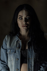 Scary woman with mad eyes in darkness