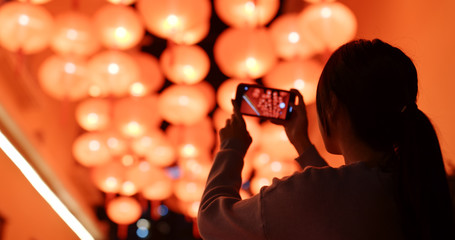 Woman take photo on cellphone under red lantern