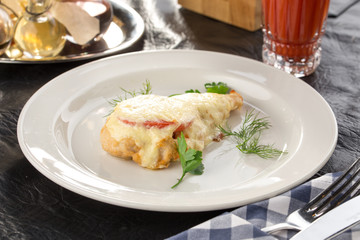 Chicken breast fillet baked with Parmesan cheese, tomato and herbs with glass of tomato juice on the table