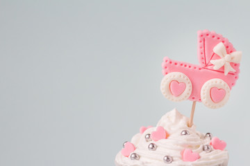 Baby shower cupcake for a girl, close up. Newborn announcement concept. Text space