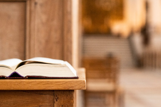 Holy book on a table in front of the altar of the church and with a view to the great big churchroom