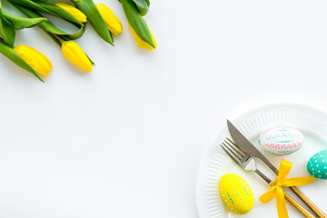 Festive Easter table decorated with tulips. Tableware and painted eggs on white background top view space for text