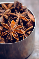 Dried anise stars in metal cup on the rustic background. Selective focus. Shallow depth of field.
