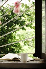 Mug of tea and book on windowsill against garden
