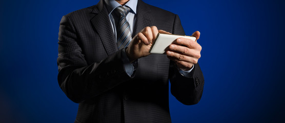 Stylish Businessman works with touch screen of his mobile phone.