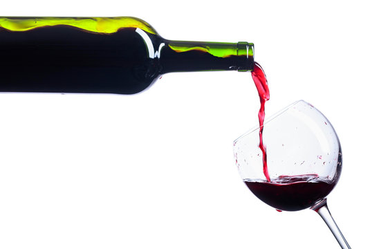 Pouring red wine from bottle to glass isolated on white.