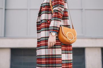Close-up of fashion details, stylish young woman wearing an overcoat with a tartan pattern and a wrist watch while holding a fancy camel bag.