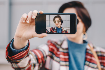 Close-up portrait of pretty and modern young fashion guru taking a selfie with her mobile phone, wearing fashionable clothes and posing for friends on social media. Focus on smartphone screen.