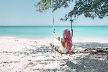 Girl with pink hair hanging on swing at beach