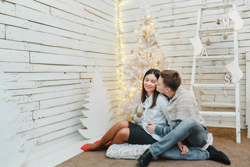 Happy couple near a christmas decoration, white background.