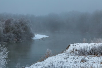 River in the fog. Forest by the river in hoarfrost, hoarfrost. Background water of the river and the forest on the shore in the fog.