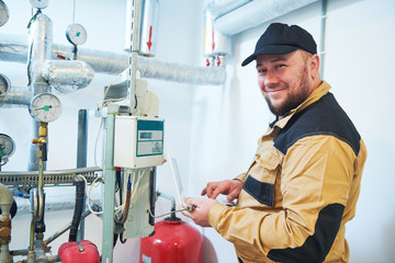 heating engineer or plumber inspector in boiler room taking readouts or adjusting meter