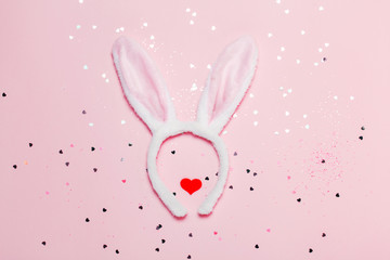Top view and flat lay of Easter symbol - bunny ears on pink background. Festive and bright, confetti and sparks.