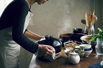 土鍋で炊いたご飯を運ぶ女性