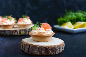 Tartlets with cream cheese and salted salmon on black background. Tasty light snack for a party. Finger Food.