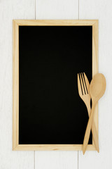 Blank chalkboard with wooden spoon and fork on white wood plank background. Styled stock photography for cookbook, food blog posts and social media content.