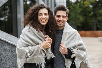 Image of beautiful couple man and woman 20s wrapped in blanket, standing over gray building outdoor