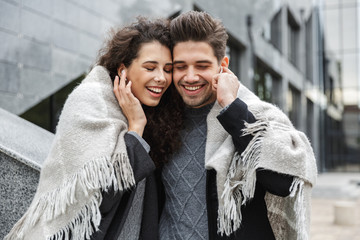 Image of european couple man and woman wearing earphones, listening to music together while standing over gray building outdoor