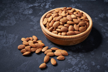 Almond  in wooden bowl on black background  , healty food