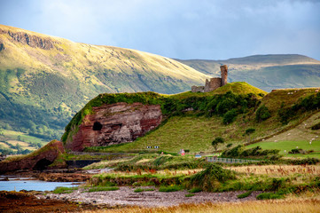 Ruins of medieval Red Bay Castle at western coast of County Antrim, Northern Ireland, UK, and a cliff near Glenariff, Watrerfoot and Cushendall at coast road A2, a.k.a. Causeway Coastal Route Fototapete