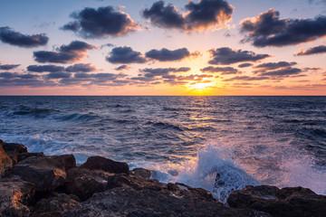 Beautiful bright sunset on the sea, rocky shore