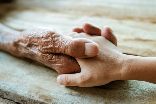Hands of the old man and a child's hand on the wood table