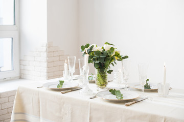 Beautiful festive table setting with elegant white flowers and cutlery, dinner table decoration