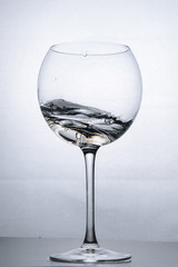 Water splashing in the luxury wine glass close up. Concept of good healthy and refreshment.