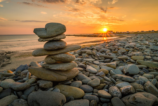 Pile of rocks kern on a beach in Penhors, Brittany, France, at sunset