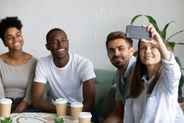 Four multiracial friends sitting in cafe taking selfie photo