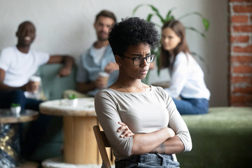 Black girl outcast sitting apart from peers in cafeteria